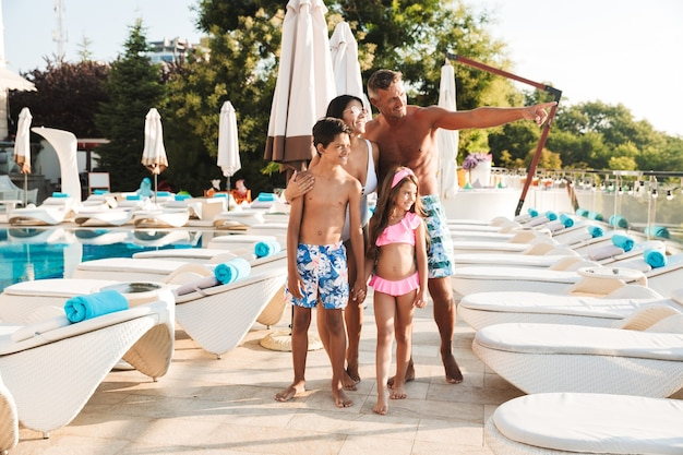 Photo of idyllic family with children resting near luxury swimming pool, with white fashion deckchairs and umbrellas during travel or spa resort