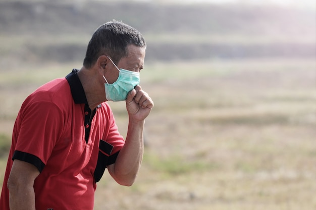 Photo illustration of a middle-aged man coughing by wearing a health mask to prevent transmission of the virus to others