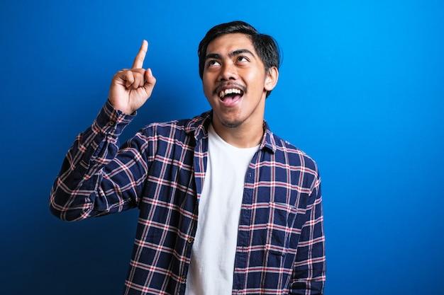셔츠를 입은 젊은 아시아 학생의 사진 이미지는 행복한 생각을 하고 위를 올려다보며 좋은 생각을 하는 것 같았습니다. 복사 공간이 있는 파란색 배경의 반신 초상화