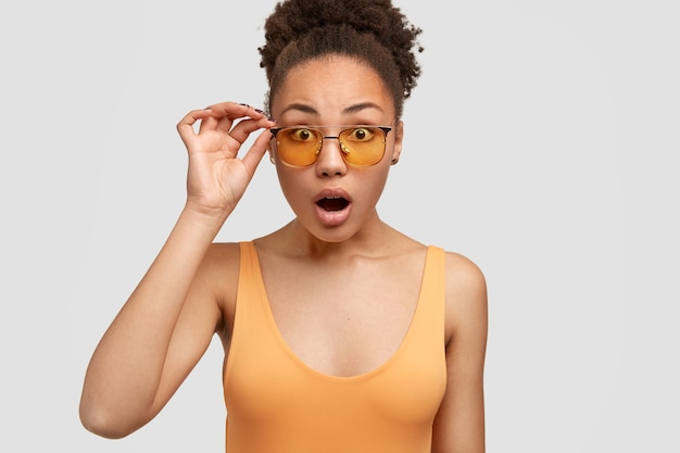 Photo of impressed black young woman opens mouth