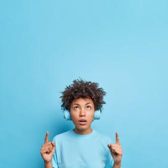 La foto di una donna dai capelli ricci impressionata dice che wow viene chiesto da qualcosa di incredibile punti sopra sullo spazio della copia mostra che la pubblicità indossa le cuffie sulle orecchie isolate sulla parete blu.
