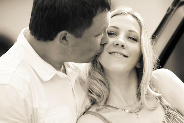 복고 스타일의 사진입니다. 갓난 아기와 함께 아내에게 키스하는 행복한 남편