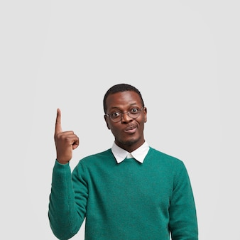 La foto di un maschio nero indeciso afferra le labbra, solleva il dito anteriore verso l'alto, si erge sul muro bianco