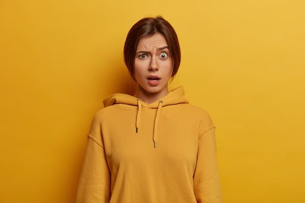 Photo of indignant young european woman raises eyebrows, has unexpected expression, smirks face, wears casual hoodie, expresses wonder, poses against yellow wall. human face expressions concept