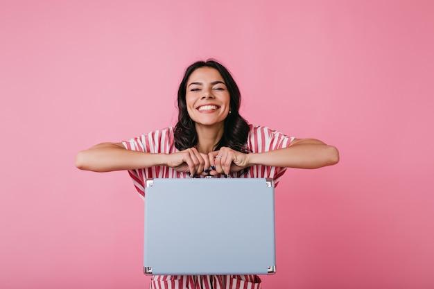 Фотография в помещении позитивной темноволосой девушки, показывающей милый чемодан для денег. леди в отличном настроении с белоснежной улыбкой.