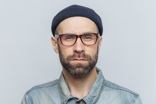 Photo of intelligent confident stylish man with dark thick beard and mustache, looks seriously