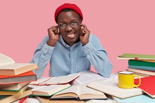 Foto di un uomo di colore irritato che stringe i denti, tappi le orecchie con entrambi gli indici, vestito con cappello rosso e camicia