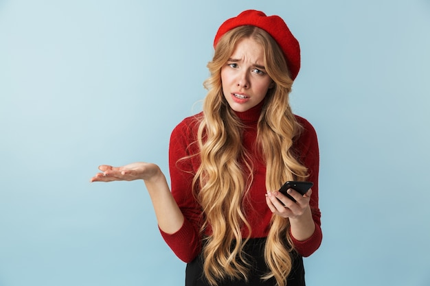 Photo of irritated girl 20s wearing red beret talking on smartphone isolated