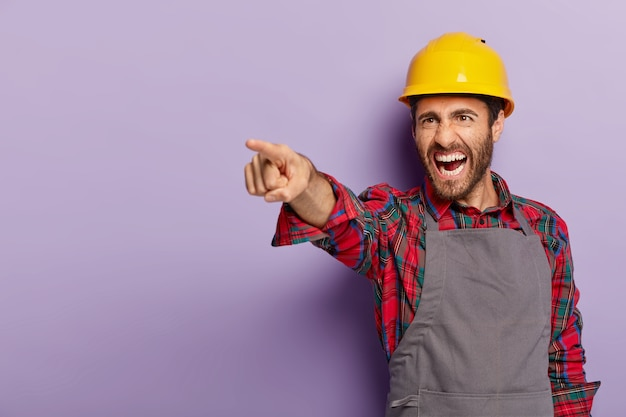 Photo of irritated manual worker points into distance, dissatisfied with result of work, wears protective hardhat and uniform, screams from annoyance, isolated over purple wall.