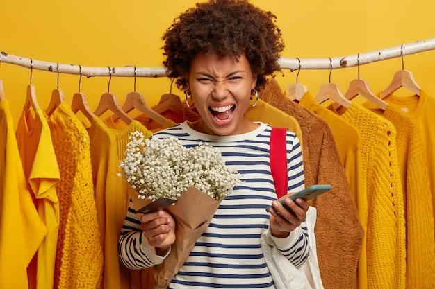 La foto di una donna irritata che ama lo shopping urla ad alta voce, non può pagare per l'acquisto, ha problemi con la transazione