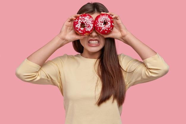 La foto di una giovane donna irritata stringe i denti con rabbia, mantiene gustose ciambelle sugli occhi, ha un aspetto piacevole, vestita con abiti casual