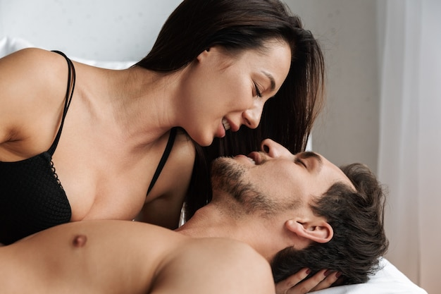 Photo of joyful couple man and woman hugging together, while lying in bed at home or hotel apartment