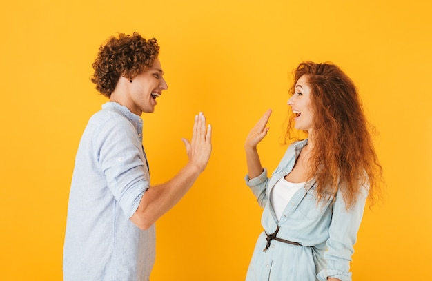 Photo of joyful couple man and woman standing face to face and giving high five, isolated over yellow background