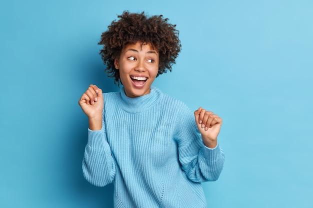 La foto di gioiosa donna dalla pelle scura balla spensierata tiene i pugni alzati sembra positivamente da parte vestita con mosse casuali del maglione