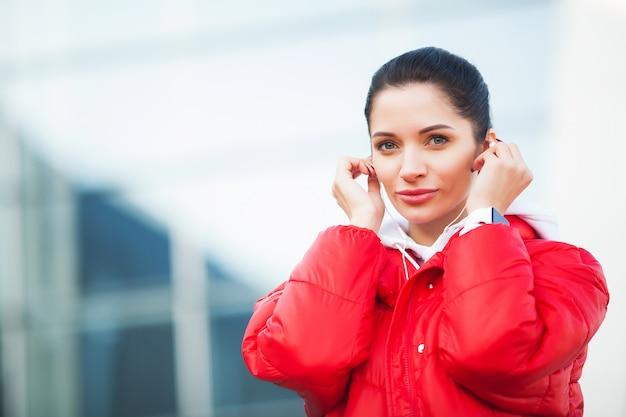 Photo of joyful fitness woman 30s in sportswear touching bluetooth earpod