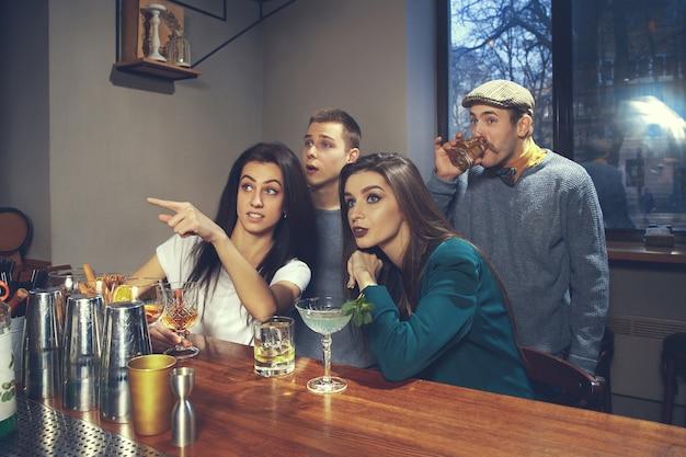 Foto di amici allegri al bar o al pub che comunicano tra loro