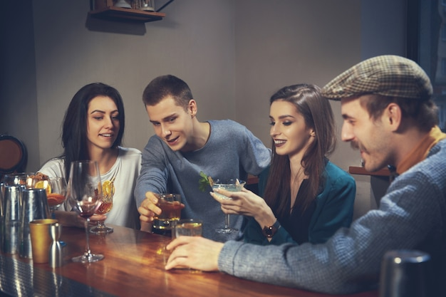 Photo of joyful friends in the bar or at pub communicating with each other