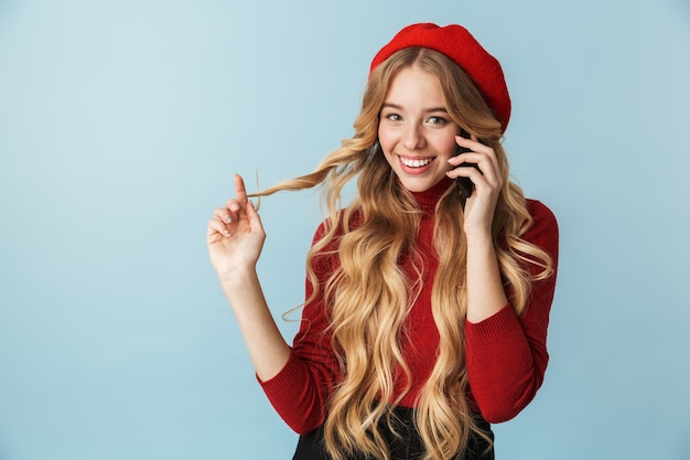 Photo of joyful girl 20s wearing red beret talking on cell phone isolated