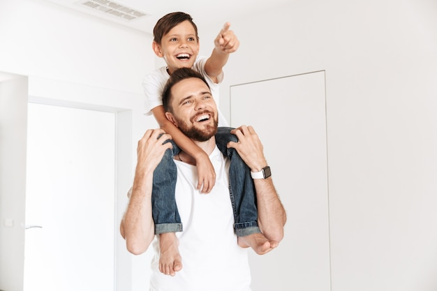 Photo of joyful happy boy sitting on the neck of his father, while looking aside indoor
