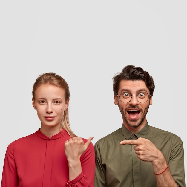 Photo of joyful hipster guy with trendy haircut, indicates with index finger at beautiful lady in red blouse. lovely couple point at each other, stand closely against white wall with free space above