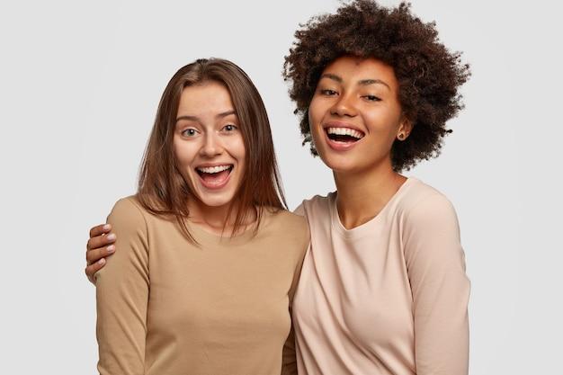 Foto di donne allegre che si abbracciano e si divertono insieme, essendo di razze diverse, vestite con maglioni casual