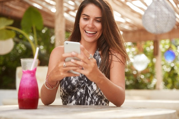 Photo of joyful lady with attractive look holds modern smart phone