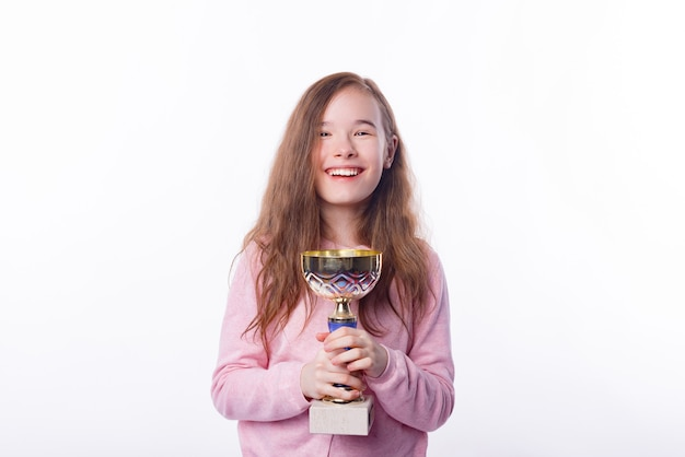 Photo of joyful little girl smiling and holding champion cup, victorious child
