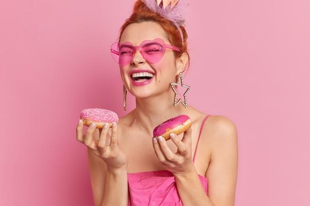 Foto di gioiosa donna alla moda rossa in sorrisi alla moda di occhiali da sole detiene ampiamente gustose ciambelle ha un debole per i dolci