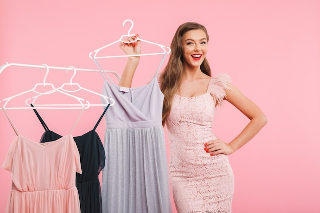 Photo of joyful young woman 20s smiling and posing near rack with lots of dresses on hangers, isolated over pink wall