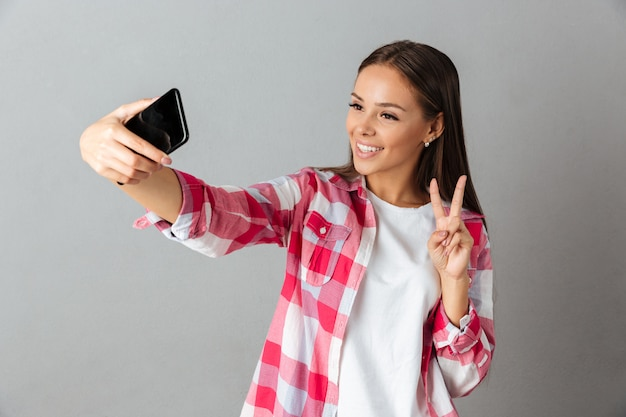 Photo of joyful young woman in checkered shirt, taking selfie by her phones