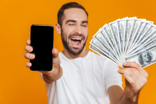 Photo of joyous man 30s in casual wear holding cell phone and fan of money, isolated