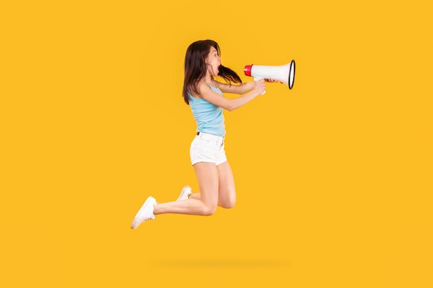 Photo of jumping girl emotionally shouting through a megaphone for marketing advertising, image on yellow wall