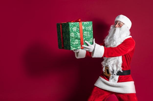 Photo of kind santa claus giving xmas present