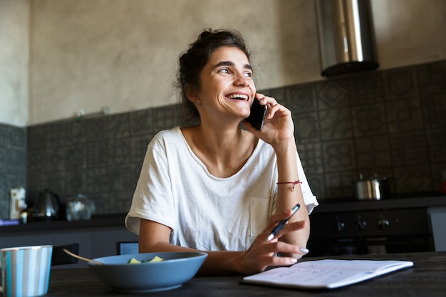 Photo of laughing brunette woman writing in diary and talking on cellphone while having breakfast in kitchen at home