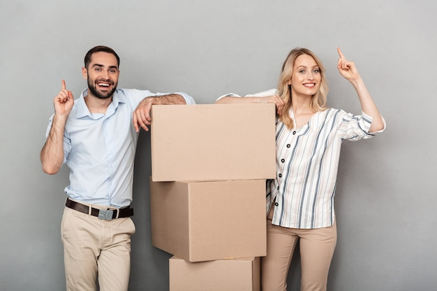 Photo of laughing couple in casual clothing standing near cardboard boxes and pointing fingers upward isolated