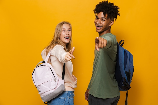 Photo of laughing students man and woman 16-18 wearing backpacks pointing fingers at you, isolated over yellow background