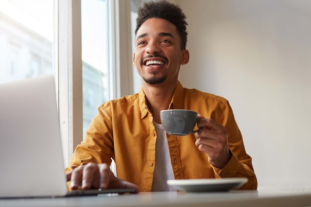 Photo of laughting african american attracrive guy, sits in a cafe, works at a laptop and drinks aromatic coffee, enjoy his freelance work.