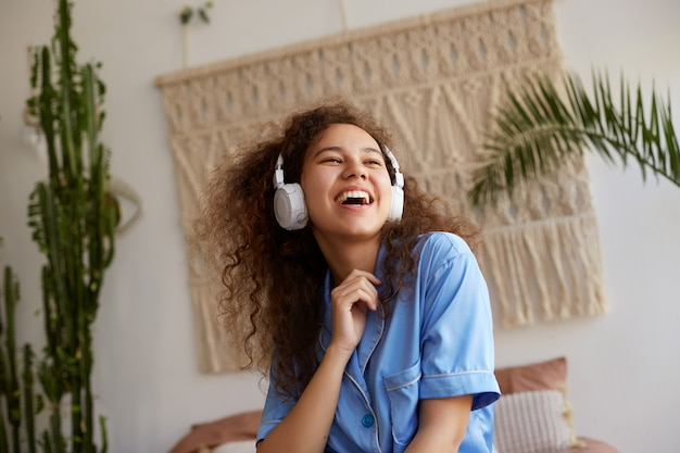 Photo of laugting curly young nice african american lady, listening favorite music in headphones, looks away and sings a song.