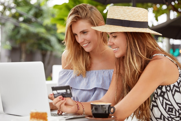 Photo of lesbian couple dressed in summer clothing, make purchase online with credit card, look with cheerful expressions at screen, spend free time at modern outdoor coffee shop. technology concept