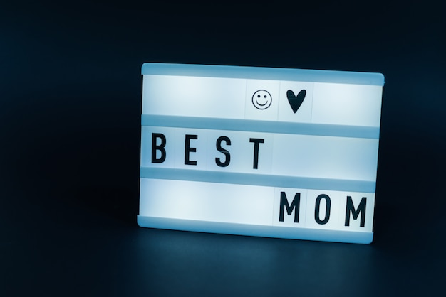 Photo of a light box with text, best mom, over isolated dark wall
