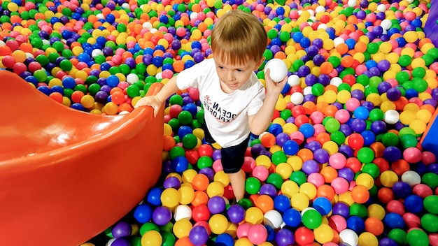 Photo of little boy playing in the pool full of colroful plastic balls. toddler having fun on playground in shopping mall