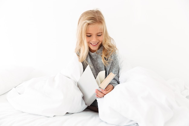 Photo of little cute girl reading book while sitting in soft bed