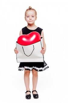 Photo of little fashionable girl in a black dress holds a big package with a heart-shaped balloon inside
