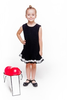 Photo of a little fashionable girl in a black dress stands next to a large package with a heart-shaped balloon inside