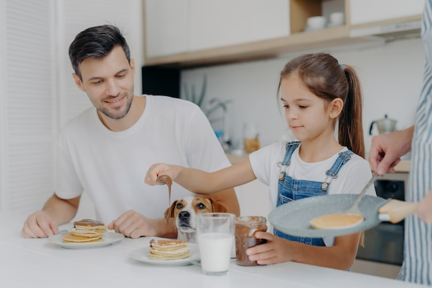 Photo of little girl in denim dungarees adds chocolate to pancakes, has breakfast together with dad and dog, likes how mother cooks. family at kitchen have breakfast during weekend. happy moment