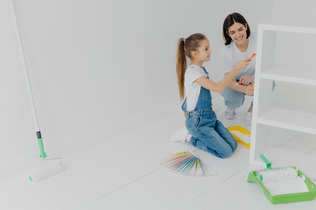 Photo of little girl and her mum paint furniture for new apartment