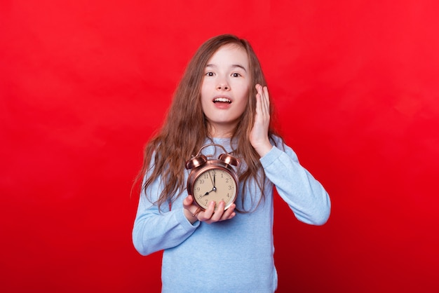 Photo of little girl late and holding alarm clock at eight a clock