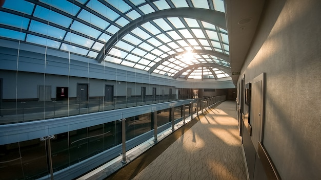 Photo of long corridors and beautiful glass roof in modern office building or hotel. sun shining through roof