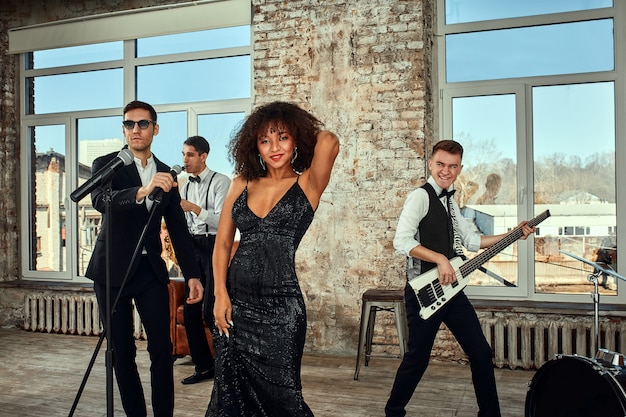 Photo of a lot of ethnic musical group in studio. musicians and an african american woman soloist posing on camera, during a rehearsal, loft