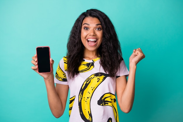 Photo of lovely amazed girl hold cellphone screen empty space raise fist wear banana print t-shirt isolated turquoise color background